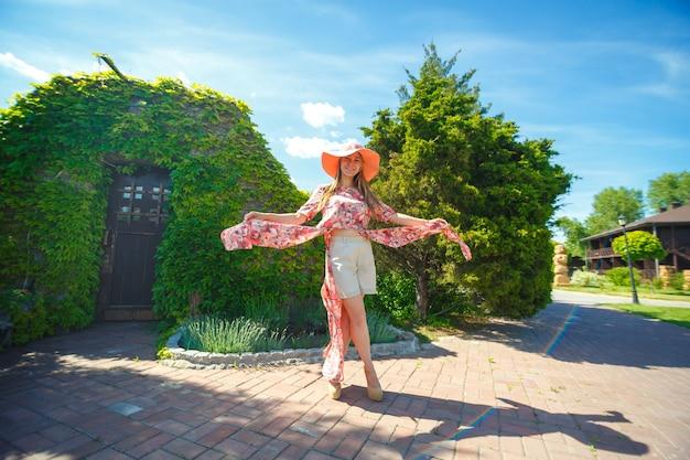 明るい夏のサンドレスとパレオの帽子をかぶった魅力的な女の子が緑豊かな公園を歩いています。