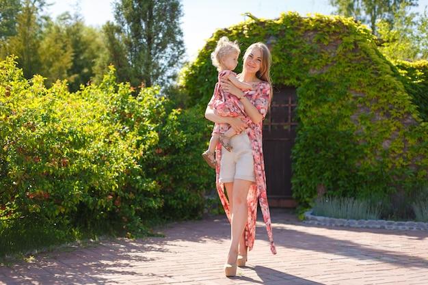 明るい夏のサンドレスを着た魅力的な女の子が、小さな娘と一緒に緑豊かな公園を散歩します。