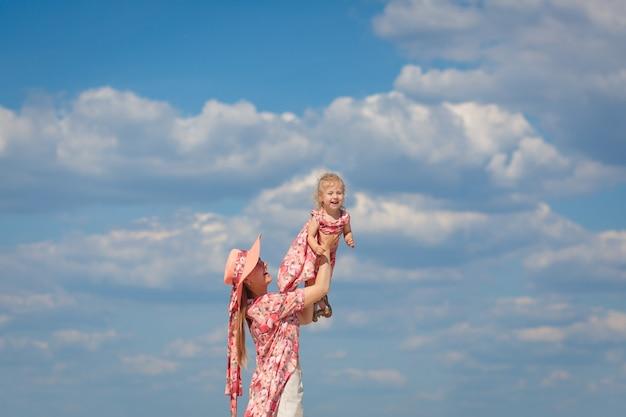 Очаровательная девушка в легком летнем сарафане гуляет по песчаному пляжу с дочкой. любит теплые солнечные летние дни.