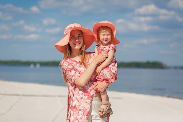 明るい夏のサンドレスを着た魅力的な女の子が、小さな娘と一緒に砂浜を歩きます。暖かく晴れた夏の日を楽しんでいます。