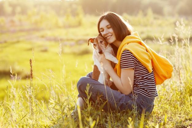 魅力的な女の子が芝生に座って、笑顔で犬を抱きしめています。