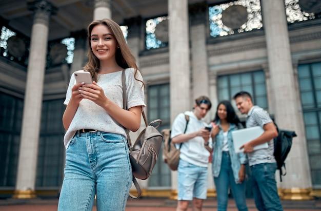 バックパックを持った魅力的な女子学生は、キャンパス近くの学生のグループを背景にスマートフォンを使用しています。