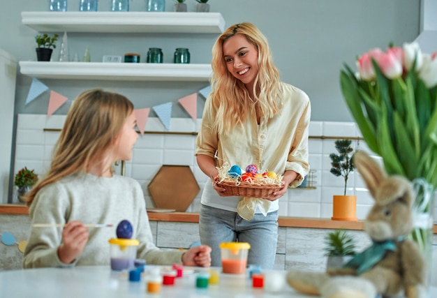 美しい母親と一緒にいる魅力的な女の子がイースターの準備をし、キッチンで卵を塗ります。キッチンで楽しんでいる母と娘。