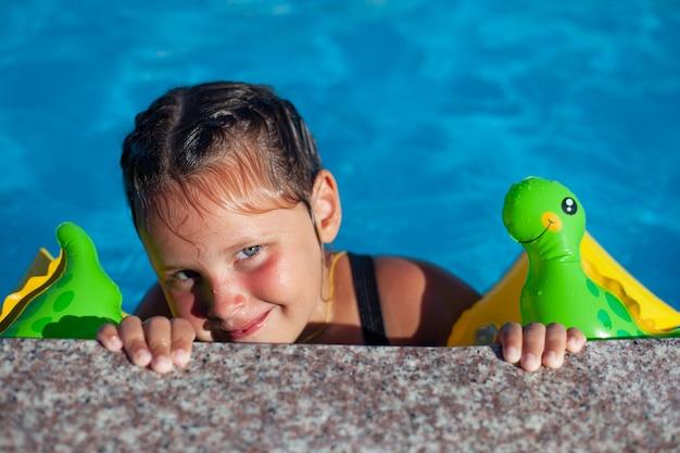 魅力的な女の子がプールの端をつかんで、優しく微笑んでいます。
