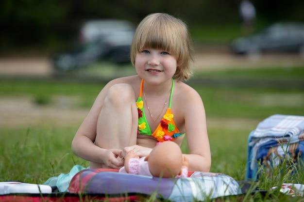 公園でのピクニック中に、明るい水着を着た魅力的な女の子がお気に入りの人形と遊ぶ