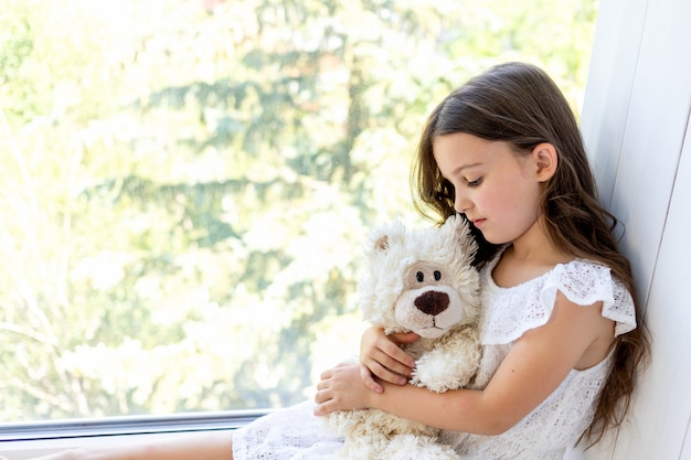 Очаровательная маленькая девочка 5-6 лет обнимает плюшевого мишку. милый ребенок дома в белой комнате, сидя у окна