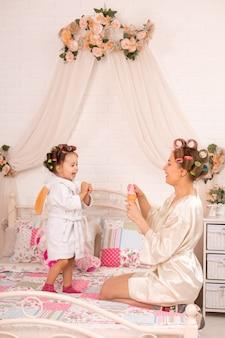 ヘアカーラーで母親と一緒にいる魅力的な少女は、石鹸ボールで遊んでいます。女性の日