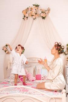 ヘアカーラーで母親と一緒にいる魅力的な少女は、石鹸ボールで遊んでいます。