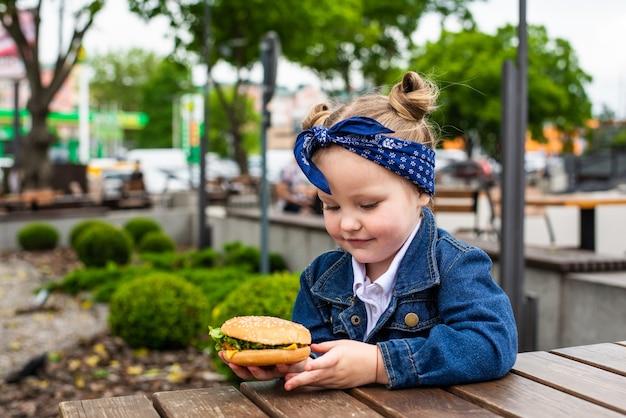 晴れた日には、笑顔のチャーミングな女の子が野外でハンバーガーを持っています。