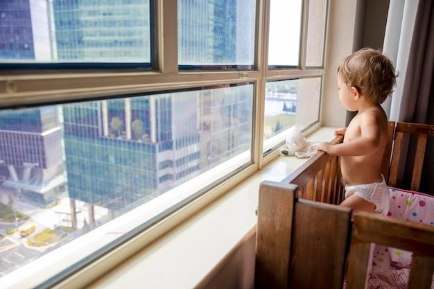 매력적인 유아가 유아용 침대에 서 있는 동안 창 밖을 내다보고 있는 유아용 침대