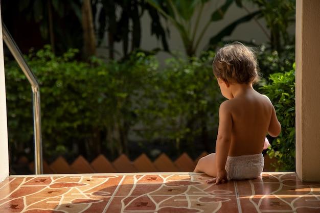 魅力的な幼児は、日光の下で緑豊かな庭園の背景にある家の階段に座っています。背面図