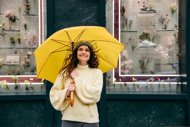 Очаровательная женщина под желтым зонтиком