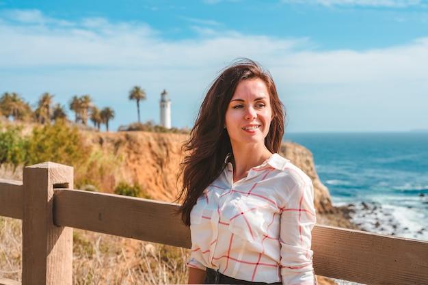 ロサンゼルスのポイント ビセンテ灯台を眺めながらウォーター フロントを歩く魅力的な女性
