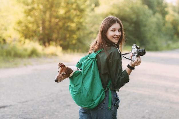 Очаровательная молодая девушка гуляет на природе, держит на плече рюкзак, из которого смотрит ее собака, и держит в руках фотоаппарат.