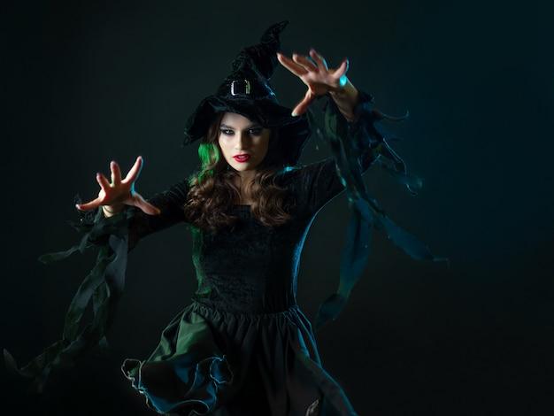 의상을 입은 매력적인 젊은 마녀가 두 손으로 마법의 패스를 만듭니다