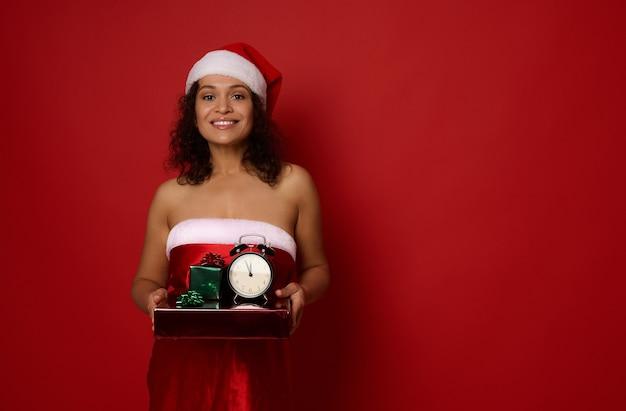 산타 카니발 드레스를 입은 쾌활한 아프리카계 미국인 여성이 크리스마스 선물과 빨간색 배경에 알람 시계를 들고 포즈를 취하고 카메라를 바라보며 이빨 미소를 짓고 있습니다. 새해 개념, 광고 복사 공간
