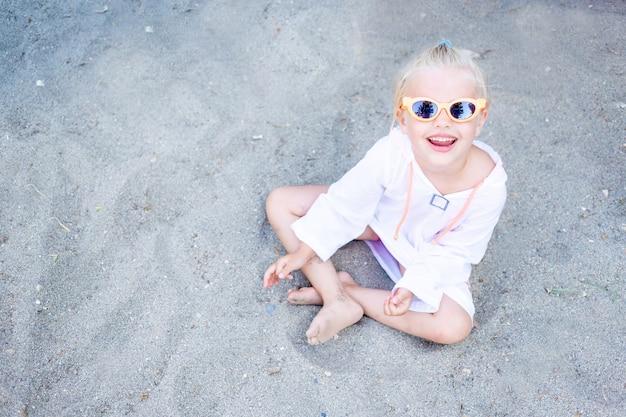 쾌활하고 즐거운 아이 소녀는 여름에 선글라스와 미소로 모래를 가지고 노는다