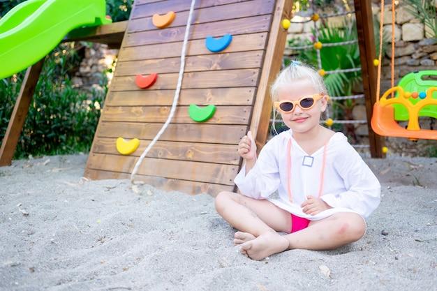쾌활하고 즐거운 아이는 여름에 선글라스를 끼고 나무 놀이터에서 모래를 가지고 노는 소녀