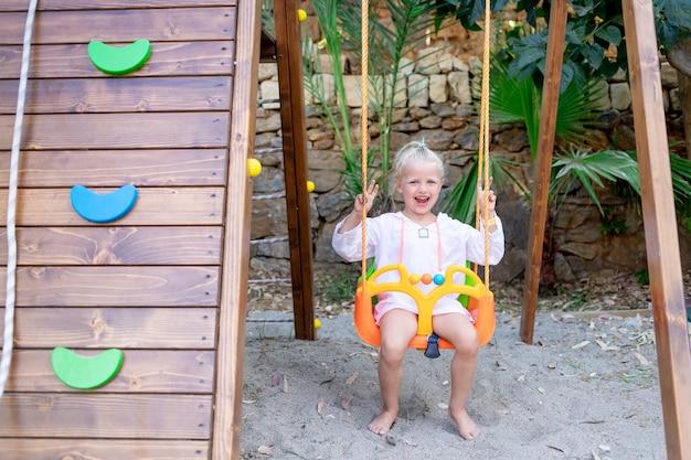 쾌활하고 즐거운 소녀는 여름에 나무 플랫폼에서 그네를 타고 미소를 짓습니다