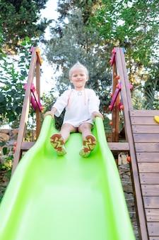 쾌활하고 즐거운 아이는 여름에 나무 플랫폼에서 미끄럼틀을 타고 굴러 떨어진다