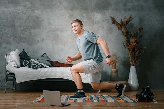 금발 머리를 가진 쾌활한 운동 선수가 온라인 교육을받은 노트북 옆 침실에서 돌진합니다. 청년은 집에서 운동하러 간다.