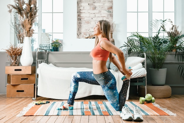 Веселая спортсменка со светлыми волосами делает выпад в спальню с онлайн-тренировкой