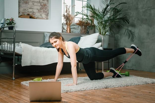 Веселая спортсменка со светлыми волосами делает выпады со спортивной фитнес-резинкой в спальне