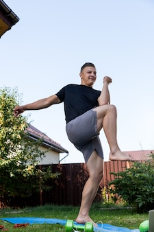 オンライントレーニングを備えたラップトップの隣で、庭でストレッチしているブロンドの髪の突進をしている陽気なアスリート。その青年は家でスポーツに出かける。