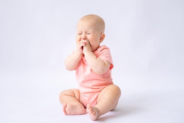 Веселый малыш в розовом боди сидит на белом фоне ребенок плачет изолировать