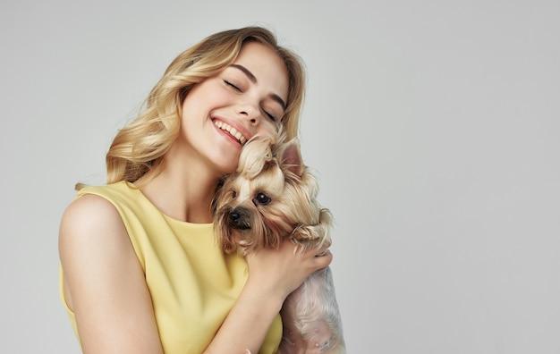Веселая блондинка в желтом платье держит на руках породистую собаку.