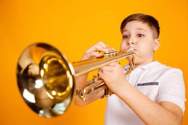 Веселый мальчик играет на трубе, дует ему в щеки. юмор играет на духовом инструменте
