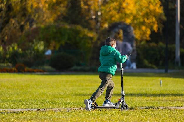 Веселый мальчик быстро катится на скутере в городском парке