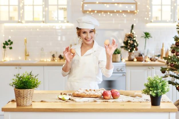陽気なシェフがかわいいエプロンでクリスマスケーキの女性料理人を準備し、卵を小麦粉に砕いて作ります...