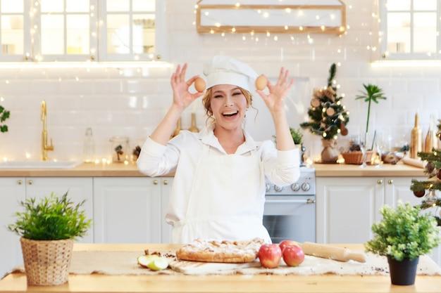 쾌활한 요리사가 크리스마스 케이크를 준비합니다. 여자는 케이크를 만들기 위해 계란을 밀가루로 깨는 귀여운 앞치마를 요리합니다. 요리의 과정입니다. 단계별로. 탁월한 휴가 전 분위기와 가정의 편안함