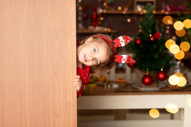 쾌활한 소녀는 새해나 크리스마스를 위한 크리스마스 트리가 있는 어두운 부엌에서 문 뒤에서 내다보고, 산타클로스 모자를 쓰고 웃고, 문자를 보낼 수 있는 공간