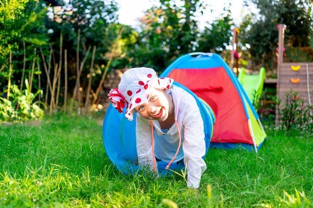 쾌활한 어린 소녀는 여름에 푸른 풀밭에서 놀이터나 집 마당에서 놀고 웃는다