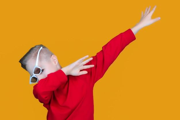 어린이용 3d 안경을 쓴 쾌활한 아이가 손을 옆으로 가리키고 있다