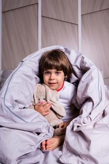 Веселый ребенок в пижаме сидит с мягкой игрушкой на хлопковом постельном белье на кровати.