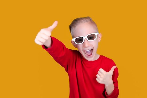 빨간 옷과 안경을 쓴 쾌활한 아이가 노란색 배경에 엄지손가락을 보여줍니다