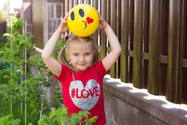 陽気な子供が家の中庭で暖かい日にトランポリンにジャンプします