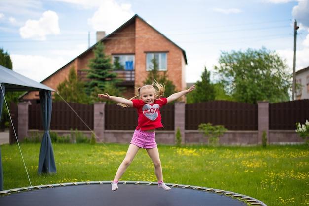 Веселый ребенок прыгает на батуте в теплый день во дворе дома