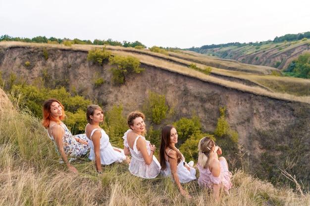 Веселая компания красивых подружек наслаждается живописной панорамой зеленых холмов на закате