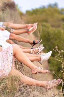 美しい女友達の陽気な会社は、崖から足をぶら下げ、絵のように美しいパノラマの景色を楽しみます。足のクローズアップ