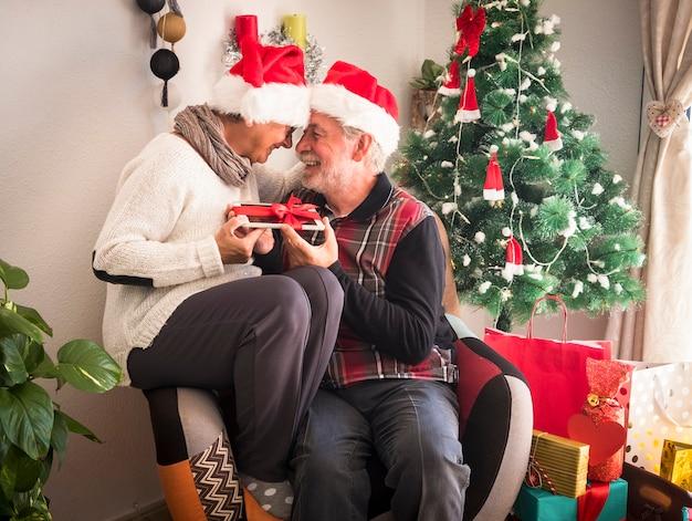 같은 안락의자에 함께 앉아 있는 산타 모자를 쓴 쾌활한 노인 부부. 크리스마스 선물로 받은 태블릿을 들고. 백그라운드에서 선물과 크리스마스 트리