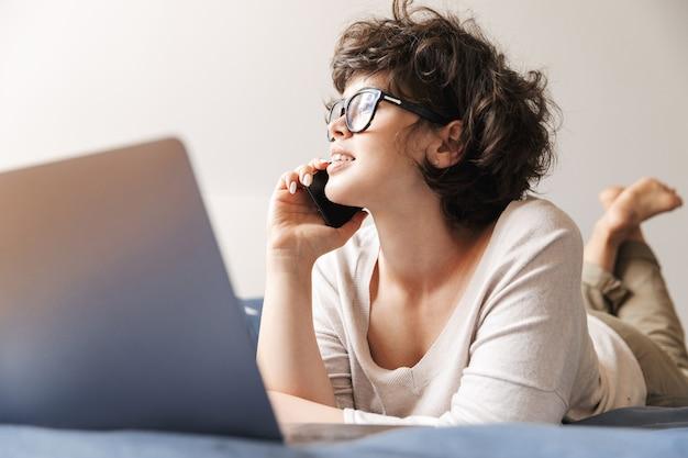 陽気なかわいい若い女性は、携帯電話で話しているラップトップコンピュータを使用してベッドの上に屋内で横たわっています。