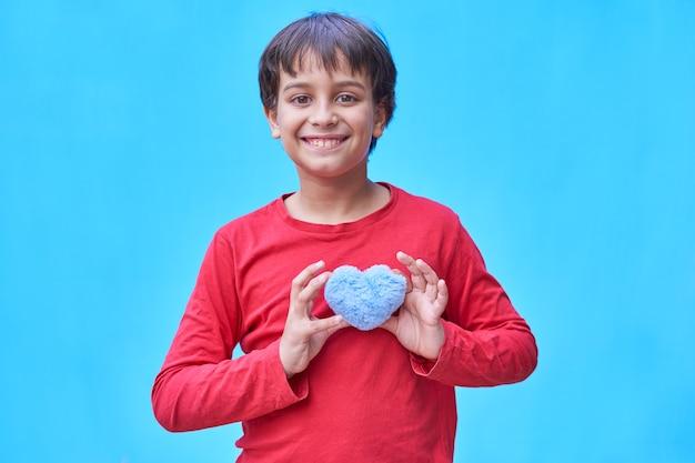 赤いシャツを着た陽気な黒髪の少年は、青い壁に青いハートのぬいぐるみを持っています