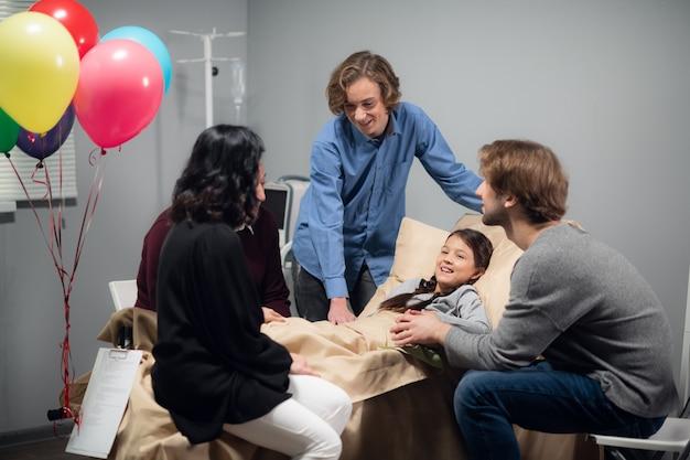 그녀의 병동에서 어린 소녀를 방문하는 쾌활한 가족.