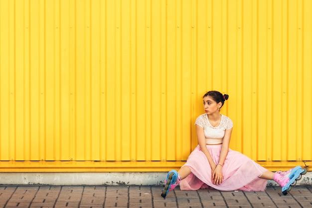 Веселая девочка ест мороженое и катается на роликах летом у желтой стены.