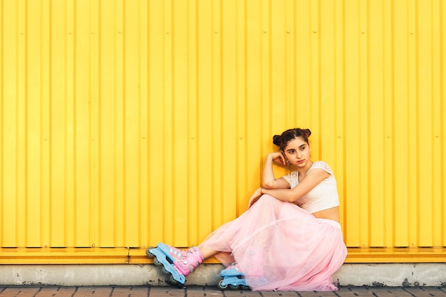 Веселая девочка ест мороженое и катается на роликах летом на фоне желтой стены