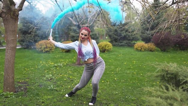 밝은 무지개 머리띠와 특이한 화장을 한 셔츠와 청바지를 입은 쾌활한 소녀. 그녀는 봄 공원을 배경으로 짙은 파란색 인공 연기에 숨어 춤을 춥니다.